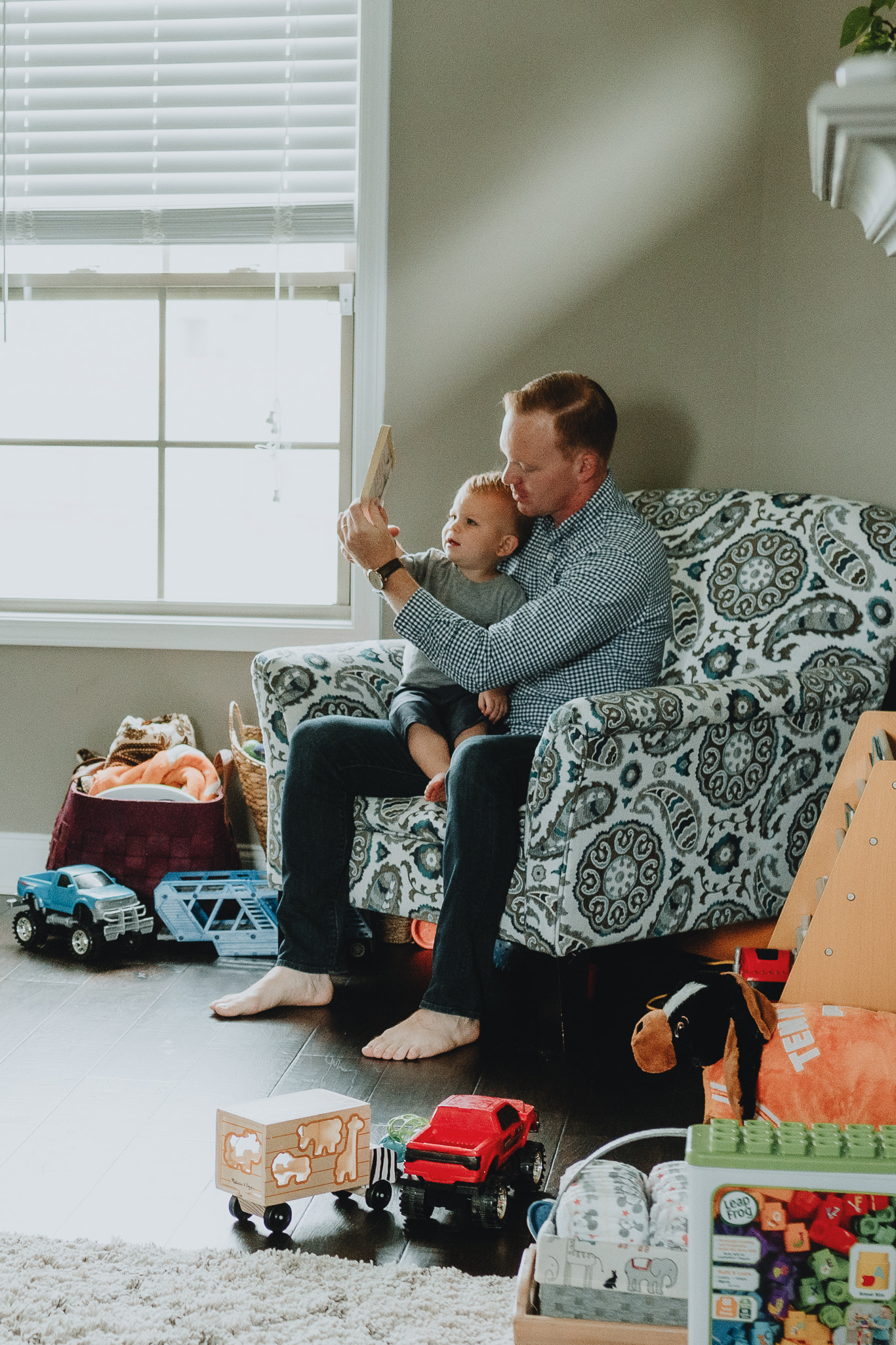 Toddler sitting in a chair with his dad | In-home family session by Five Pence Photography | Nashville Baby Guide